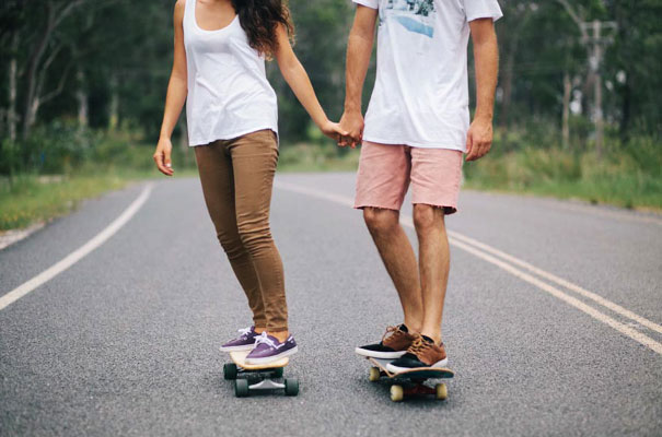 skateboarding couple holding hands